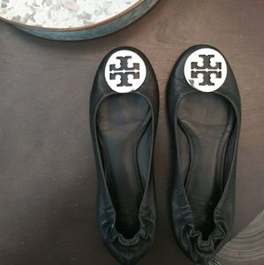 Black tory burch flats with silver emblem.